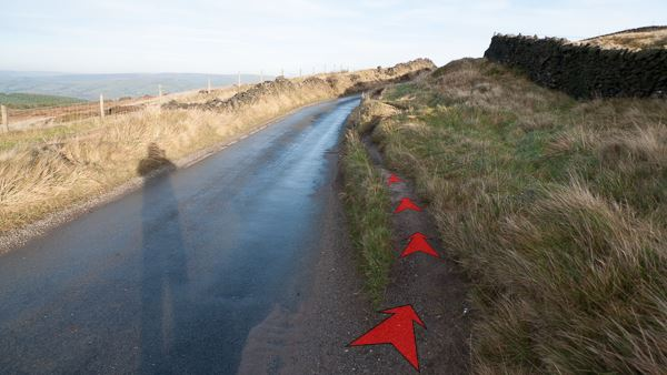 A photo of step 3 of the Cats Tor route, with red arrows superimposed to show the way.