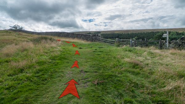 A photo of step 6 of the Shining Tor route, with red arrows superimposed to show the way.