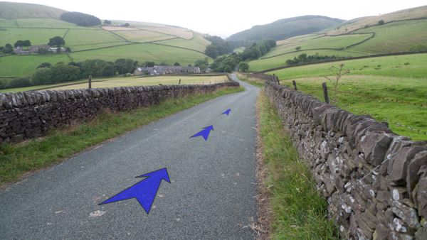 A photo of step 11 of the Three Shires Head route, with blue arrows superimposed to show the way.