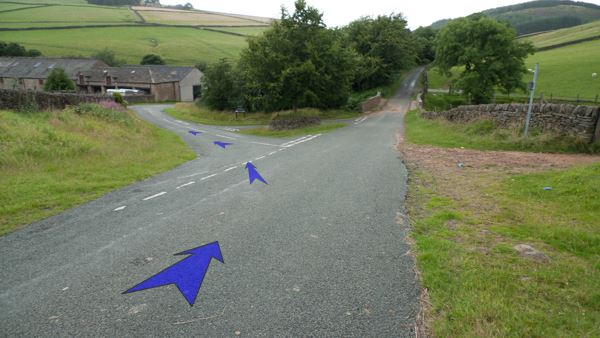 A photo of step 12 of the Three Shires Head route, with blue arrows superimposed to show the way.