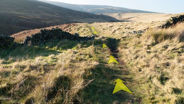 A photo of step 1 of the Wildmoorstone Valley route, with yellow arrows superimposed to show the way.