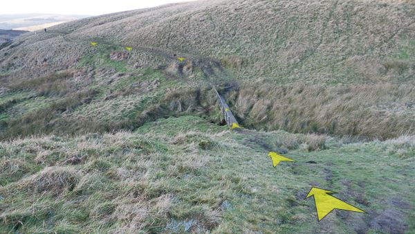 A photo of step 2 of the Wildmoorstone Valley route, with yellow arrows superimposed to show the way.